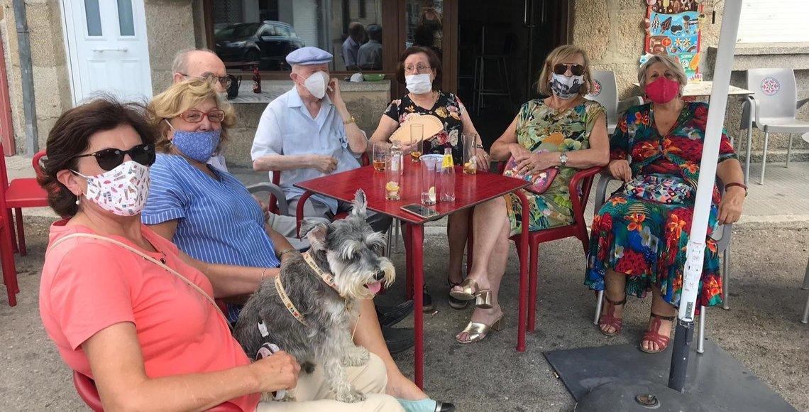 Un grupo de veraneantes disfrutan de un aperitivo en un bar de Cualedro